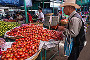 A Mexican man buys fresh tomatos at Benito Juarez market in Oaxaca, Mexico.