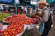 A Mexican man buys fresh tomatos at Benito Juarez market in Oaxaca, Mexico.