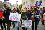 Women with banners and roses at start of the Bread and Roses Womens March on January 19, 2019 in London, England.  The event was dubbed the Bread and Roses March based on the strikes of the same name by textile workers in Massachusetts in 1912 and Bread and Roses is the title of a poem by American poet James Oppenheim about the strikes.