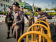 07 JULY 2015 - BANGKOK, THAILAND:  Thai police walk through a military checkpoint in front of the Ministry of Defense in Bangkok before a rally to support students arrested by the military. About 100 people gathered in front of the Ministry of Defense in Bangkok Tuesday to support 14 university students arrested two weeks ago for violating orders against political assembly. They're facing criminal trial in military courts. The courts ordered their release Tuesday because they can only be held for two weeks without trial, the two weeks expired Tuesday and the military court chose not to renew their pretrial detention. The court order was not an acquittal. They still face trial and possible prison sentences if convicted.       PHOTO BY JACK KURTZ