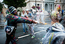 © London News Pictures. 25/08/2012. London, UK. Revelers enjoy a paint, flour and egg fight which traditionally marks the beginning of Children's Day on day one of the Notting Hill Carnival in West London on August 25, 2013.  The annual carnival, which is the largest of its kind in Europe, is expected to attract around 1 million people. Photo credit : Ben Cawthra/LNP