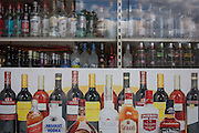 A detail of an off-licence's window showing bottles of wines and spirits, in south London.