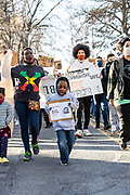 A child holds a sign and chants during a march protesting the police killing of Osaze Osagie.