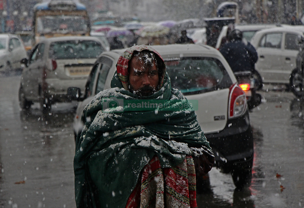 November 3, 2018 - Srinagar, Jammu and Kashmir, India - SRINAGAR, KASHMIR, INDIA-NOVEMBER 03 : A non- local man walks as it snows in Srinagar the summer capital of Indian controlled Kashmir on November 03, 2018. The season's first snowfall has forced authorities to suspend vehicular traffic on Srinagar-Jammu National Highway.Air traffic was also stopped due to snowfall with several flights cancelled, the officials said. (Credit Image: © Faisal Khan/ZUMA Wire)