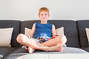 Young, confident red haired boy of seven lounging on the sofa indoors
