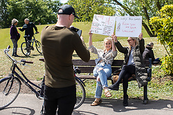 """© Licensed to London News Pictures. 16/05/2020. Manchester, UK. Two women hold placards reading """" No mandatory vaccines """" , """" Beware Poison """" """" No 5G """" and """" Hey Bill Gates Fuck you and your vaccine """" . An anti-lockdown, """"mass gathering"""" demonstration is held in Platt Fields Park in protest at government measures to control the spread of Covid-19. A group calling itself the UK Freedom Movement has organised a series of demonstrations across the UK. Photo credit: Joel Goodman/LNP"""
