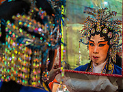 """26 NOVEMBER 2014 - BANGKOK, THAILAND: A Chinese opera performer checks her headdress in a mirror at the Chow Su Kong Shrine in the Talat Noi neighborhood of Bangkok. Chinese opera was once very popular in Thailand, where it is called """"Ngiew."""" It is usually performed in the Teochew language. Millions of Chinese emigrated to Thailand (then Siam) in the 18th and 19th centuries and brought their culture with them. Recently the popularity of ngiew has faded as people turn to performances of opera on DVD or movies. There are about 30 Chinese opera troupes left in Bangkok and its environs. They are especially busy during Chinese New Year and Chinese holidays when they travel from Chinese temple to Chinese temple performing on stages they put up in streets near the temple, sometimes sleeping on hammocks they sling under their stage.      PHOTO BY JACK KURTZ"""
