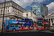 Multi-coloured London buses pass each other at Bank triangle beneath the Bank of England.