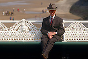 A rather eccentric-looking man is seated on a bench on Blackpool's North Pier. This northern seaside resort in the north-west of England is diverse in its transient holiday population whose behaviour can be routinely odd. The pier has intricate cast ironwork seat backs dating from 1863 and the man sits with ankles crossed, wearing a suit and trilby hat on a warm summer's day. In the background we see families - parents and children - playing and walking on the beach at low-tide - the golden sands a much-visited aspect of Blackpool, the largest resort in the north of England and visited traditionally by working people from industrial towns and cities during the industrial revolution.