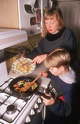 Mother and young son cooking together in kitchen,