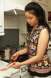 Woman trimming fat from bacon in kitchen,