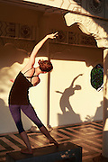 A young woman casts a shadow  while doing a side bend during an evening yoga session.