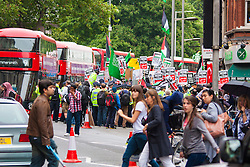 """London, July 5th 2014. Shoppers cross the street while in the background hundreds protest near the Israeli embassy in London against the ongoing occupation of Palestine and the west's support of """"Israel's collective punishment of Palestinians""""."""