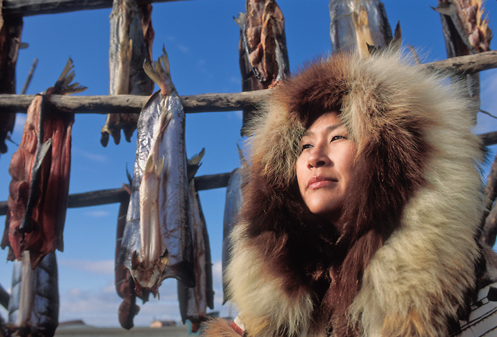 Inupiat woman in traditional fur parka with drying salmon, Kotzebue, Alaska.
