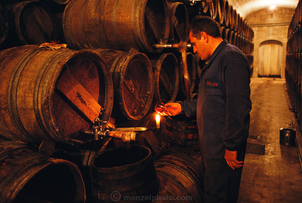 Racking wine at Bodegas Muga, in Haro, Rioja, Spain.  Cellar workers check clarity and color by candlelight.