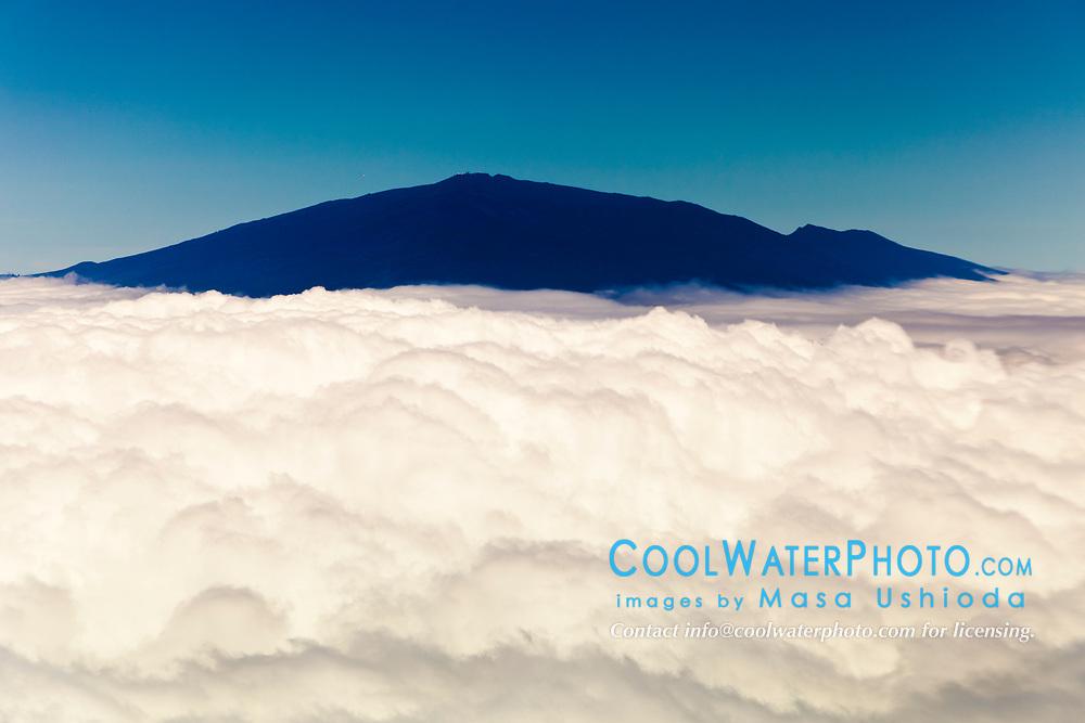 Haleakala or the East Maui Volcano, elevation of 10,023 ft (3,055 m), standing above massive clouds, Maui, Hawaii, USA