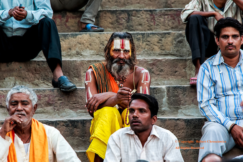 Standing Out In A Crowd: A full bearded Sadhu, with his face and arms painted red white and yellow, sits conspicuously awaiting the Hindu Aarti ceremony to start, riverside in Varanasi India.