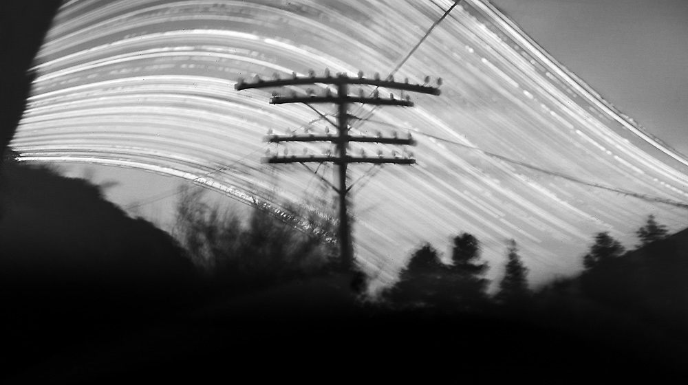 """Abandoned power pole; Port Hills.<br /> 2016 (6 months pinhole exposure).<br /> 140mm x 250mm (image size).<br /> Pigment ink on paper.<br /> Editions of 5. First shown at the exhibition """"Art for Art"""" at the Christchurch Art Gallery Te Puna o Waiwhetū (2017)."""