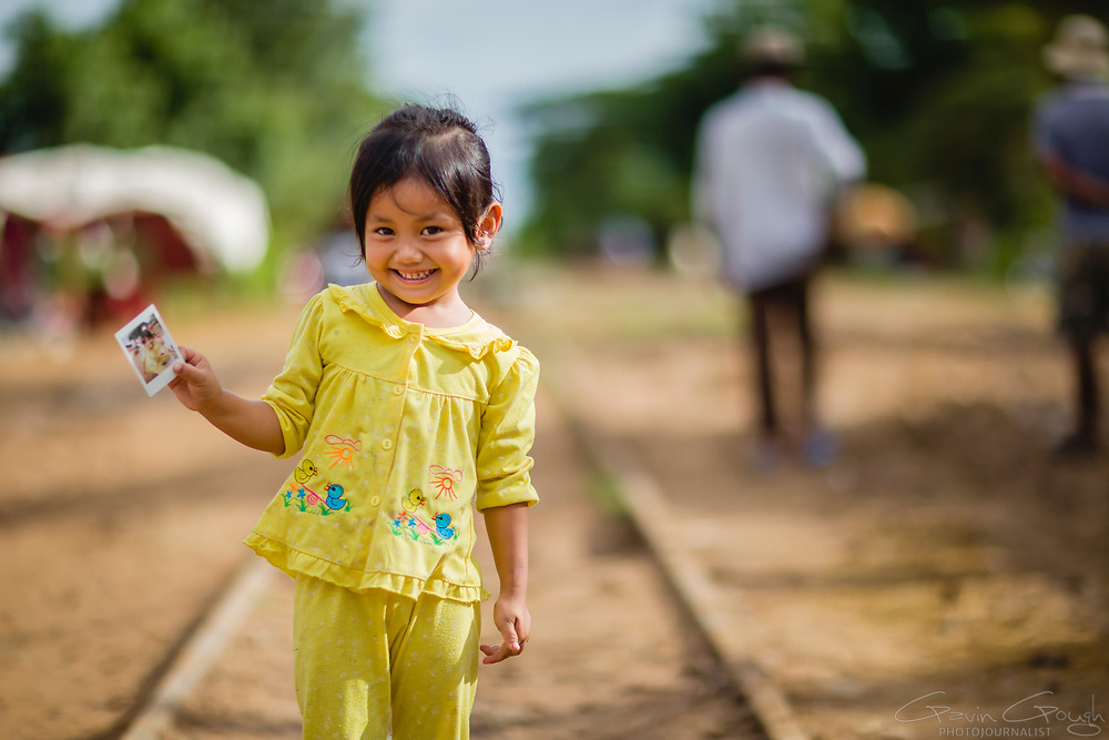 A young girl holding an instant photo of herself standing on a railway line, Sangkae, Battambang, Cambodia