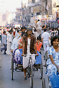 Rickshaw drivers and shoppers in busy street market in Delhi, India