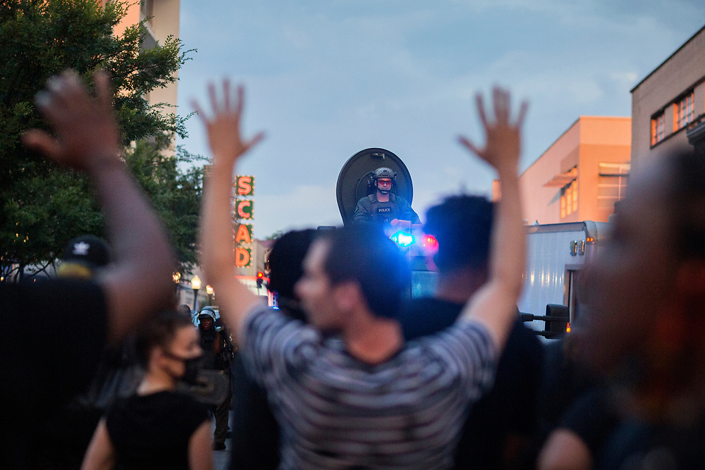 """SAVANNAH, GA - MAY 31, 2020: Protesters hold hands up and chant """"don't shoot"""" during a stand off with Savannah Police SWAT after a peaceful rally, Saturday and joining a national outrage over the death of George Floyd. Floyd died in police custody on Memorial Day in Minneapolis. (AJC Photo/Stephen B. Morton)"""