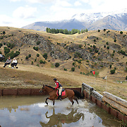 Lara Coker riding Darchiac in action at the water jump during the Cross Country event at the Wakatipu One Day Horse Trials at the Pony Club grounds,  Queenstown, Otago, New Zealand. 15th January 2012. Photo Tim Clayton