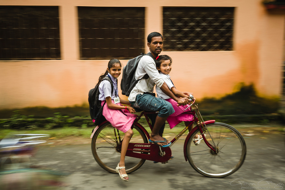 A father and his two schoolgirl daughters cycle home at the end of the school day, Sarsuna Girls' High School, Kolkata, India