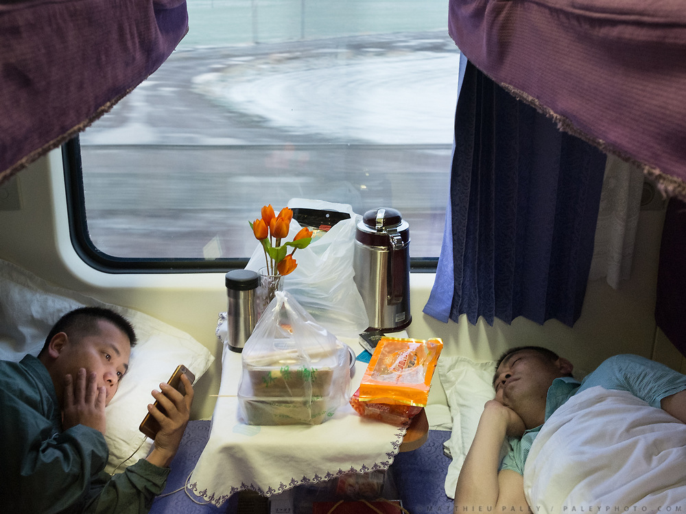 A man checks his mobile phone in the train crossing the Tibetan plateau. Life in the sleeping compartments in the train from Hong Kong to Urumqi, Xinjiang.