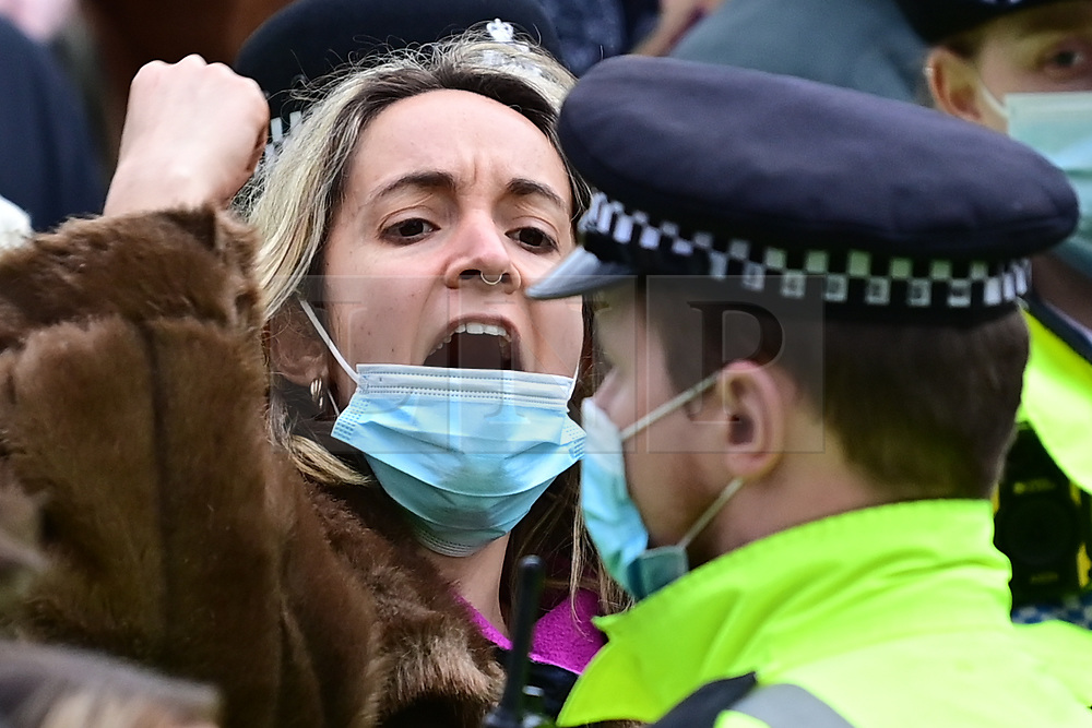 © Licensed to London News Pictures. 14/03/2021. London, UK. A protestor scremas in the face of a police officer outside New Scotland Yard in London during a demonstration, organised by Sisters Uncut, against the actions of the police force at a vigil for murdered Sarah Everard yesterday evening. There have been calls for Met Chief Cressida Dick to resign following yesterday's scenes, when police dragged women away from a bandstand as thousands gathered in Clapham, South London. Photo credit: Ben Cawthra/LNP