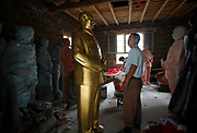 "A workers looks up at a statue of Mao Zedong at the workshop of a ""Red"" memorabilia collector and manufacturer, near Mao's birthplace in Shaoshan, Hunan Province, China on 12 August 2009.  The workers were once electricians. The village of Shaoshan, in rural Hunan Province, is tiny in size but big in name. It was the childhood home for Mao Zedong, the controversial revolutionary who came from obscurity but eventually defied all odds conquered China in the name of communism. Now his home, a sacred place among China's official propaganda, is in reality a microcosm of the country itself: part commercialism, part superstition, with a dash of communist ideological flavor."