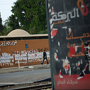 An egyptian man passes by campaign posters at Cairo's Masr El Gdeeda district.