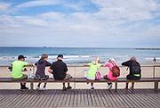 Eldery people socializing on a bench near the beach of Pineda de Mar, Spain