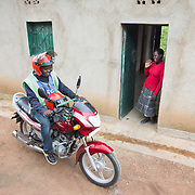 CAPTION: Jean Claude's younger sister Claudine waves him off from home, as he heads out for his day's work as a motorcycle taxi driver. This bike is symbolic of better times that have recently arrived. The siblings were orphaned at a young age, and both suffered a difficult childhood. While Jean Claude left for Kigali to seek a domestic job at the age of 15, his sister was taken care of by their aunt's family, who lived nearby. Claudine had to take on a lot of household work at the aunt's home, rather like what a maid would be expected to do, but she didn't feel she could complain much as the family had offered to provide for her. She had to work hard, collecting firewood, bringing water and taking care of the children. Jean Claude came back from Kigali around 2011-12, just before Concern Worldwide's Graduation Programme was rolled out. He'd been feeling that life wasn't improving in Kigali, and wanted to be there to take care of his sister. The two are very close, and Jean Claude says he feels responsible for Claudine. LOCATION: Kabuga Village, Gafumba Cell, Rusatira Sector, Huye District, South Province, Rwanda. INDIVIDUAL(S) PHOTOGRAPHED: Jean Claude Minani (left) and Claudine Iradukunda (right).