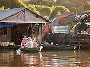 Women transporting hot food in their boat. They live in one of the floating village communities on the Tonlé Sap lake, Cambodia