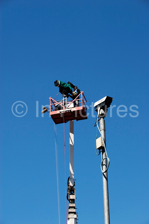 TV camera man filming from atop a crane beside a security CCTV camera. During the London Marathon.