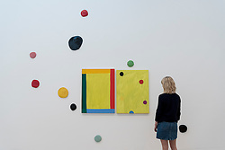 "© Licensed to London News Pictures. 07/06/2016. London, UK.   A staff member views ""Good Vibrations Diptych, Remembering David"", by the American artist Mary Heilmann, which is previewed ahead of her first major UK exhibition, ""Looking at Pictures"", at the Whitechapel Gallery.  The exhibition spans the artist's five decade career, from her early geometric paintings made in the 1970s to her recent shaped canvases in day-glo colours.  The show features approximately 45 paintings as well as a selection of ceramics, chairs and works on paper, many of which have never been exhibited.  Photo credit : Stephen Chung/LNP"