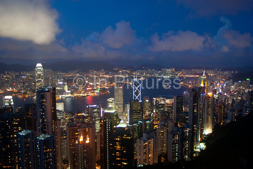 Evening view from Victoria Peak, Hong Kong. From this classic viewpoint the entire view across Hong Kong Harbour can be seen. The view sweeping down through Mid-levels to Central, along to Causeway Bay, all the way along Hong Kong Island's coast across North Point, Quarry Bay to Wan Chai. Also over the water we see the Chinese mainland area Kowloon. A deep blue Hong Kong sky forms a backdrop for the forming clouds which are lit up by Two International Finance Centre, Hong Kong's tallest building at 415m.