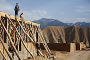 Afghans are building a small local Mosque in a rocky village located near Bamyian's archaeological site. The cliff where once stood the Western Buddha (55m - 'Male') is photographed after sunset in Bamiyan, Afghanistan, an area mostly populated by Hazaras. The Buddhas of Bamiyan were two 6th century monumental statues of standing Buddhas carved into the side of a cliff in the Bamiyan valley in the Hazarajat region of central Afghanistan, situated 230 km northwest of Kabul at an altitude of 2500 meters. The statues represented the classic blended style of Gandhara art. The main bodies were hewn directly from the sandstone cliffs, but details were modelled in mud mixed with straw, coated with stucco. Amid widespread international condemnation, the smaller statues (55 and 39 meters respectively) were intentionally dynamited and destroyed in 2001 by the Taliban because they believed them to be un-Islamic idols. Once a stopping point along the Silk Road between China and the Middle East, researchers think Bamiyan was the site of monasteries housing as many as 5,000 monks during its peak as a Buddhist centre in the 6th and 7th centuries. It is now a UNESCO Heritage Site since 2003. Archaeologists from various countries across the world have been engaged in preservation, general maintenance around the site and renovation. Professor Tarzi, a notable An Afghan-born archaeologist from France, and a teacher in Strasbourg University, has been searching for a legendary 300m Sleeping Buddha statue in various sites between the original standing ones, as documented in the old account of a renowned Chinese scholar, Xuanzang, visiting the area in the 7th century. Professor Tarzi worked on projects to restore the other Bamiyan Buddhas in the late 1970s and has spent most of his career researching the existence of the missing giant Buddha in the valley.
