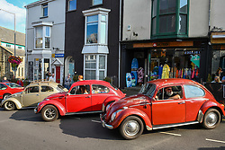 © Licensed to London News Pictures. 27/08/2021. Swansea, UK. VW Beatles line the street in the village of Mumbles in Swansea, as it is taken over by vintage cars. The event saw the main street closed to traffic and full of historic vehicles and replicas, ranging from E-Type Jaguars, to modern day classics Photo credit: Robert Melen/LNP