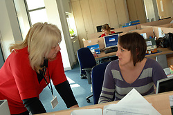 Manager and trainee talk in an open plan office at a Housing Association