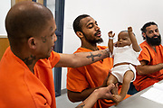 """Keith Spike (C) reacts to holding a mannequin during a lesson on how to properly cradle an infant as part of a parenting class at Falkenburg Road Jail in Tampa, Florida, U.S., December 28, 2015. Spike's story is one of redemption. He's been locked up more than twenty times, entrenched in a cycle of incarceration. During this latest stint—nine months for drug possession and probation violation—Spike enrolled in the parenting class. He has a 6-year old daughter, Carolyn, who cries at night without him. Spike calls her his pride and joy, saying she's his motivation for attending the course. This time, he wants a real fresh start, for Carolyn. """"It's not too late—because my daughter, she still young—I still got a chance to make up."""""""
