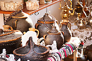 The busy old market bazaar street Kujundziluk with lots of tourist craft and art shops and street merchants. Souvenir shop selling traditional black glazed earthenware cooking pots. Historic town of Mostar. Federation Bosne i Hercegovine. Bosnia Herzegovina, Europe.