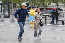 May 4, 2019 - London, UK, UK - London, UK. A couple runs for shelter as it starts to rain suddenly in Trafalgar Square. (Credit Image: © Dinendra Haria/London News Pictures via ZUMA Wire)