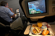 A man tucks in to his in-flight meal on-board an Air France Boeing 777 flight from Paris Orly to Cayenne, French Guiana. Putting more food into his mouth while watching an in-flight movie, the male passenger has an aisle seat on this airliner. We also see on another seat back, the progress of this journey across the Atlantic Ocean towards the mainland of South America, seen on the moving map system screen which reveals statistics such as altitude, airspeed, distance to destination, distance from origination and local time. Using GPS avionics, the capital Cayenne is seen as the destination as well as Caracas, Georgetown, Kingstown and San Juan in the Caribbean. On the viewer's lowered tray is a light lunch of fruit, natural yoghurt, bread roll, orange juice and empty up. This is the best of Economy class.