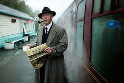 © Licensed to London News Pictures. <br /> 15/10/2016. <br /> Grosmont, UK.  <br /> <br /> A man in 1940's clothing reads a newspaper on the station platform at Grosmont station during the North Yorkshire Moors Railway Wartime Weekend event. <br /> The annual event brings together re-enactors and enthusiasts along the length of the NYMR heritage steam railway line to recreate the feel of the war years of the 1940's. <br /> <br /> Photo credit: Ian Forsyth/LNP