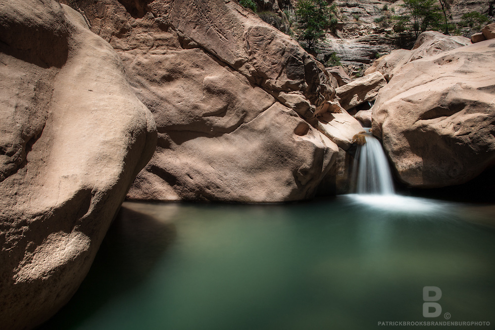 A natural turquoise, fresh waterfall in Torotoro Canyon of Torotoro National park in central Bolivia, smoothly flows between large bolders in an idealic oasis.
