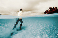 Underwater split level view of fully clothed man trawls through water towards an island. shot on infrared film. Tonga