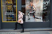 Woman on her cell phone looks as though she is being pursued by a photo of a runner in a gym window in London, England, United Kingdom.