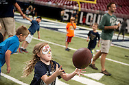 2 AUG. 2014 -- ST. LOUIS -- Seven-year-old Adrana Hall (center) tosses a football with her father Kevin Hall (not pictured) of St. Peters on the playing field at the Edward Jones Dome in St. Louis during the 2014 St. Louis Rams Fan Fest Saturday, Aug. 2, 2014. The day included games and tours, and a scrimmage by the Rams. Photo © copyright 2014 Sid Hastings.