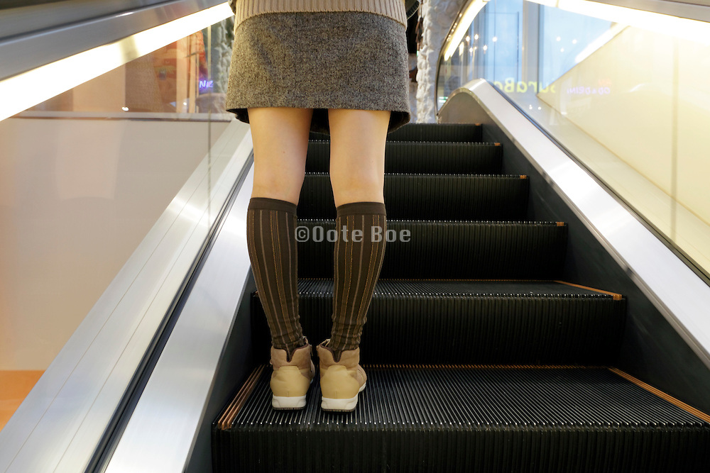 Japanese young female person wearing striped socks going up an escalator